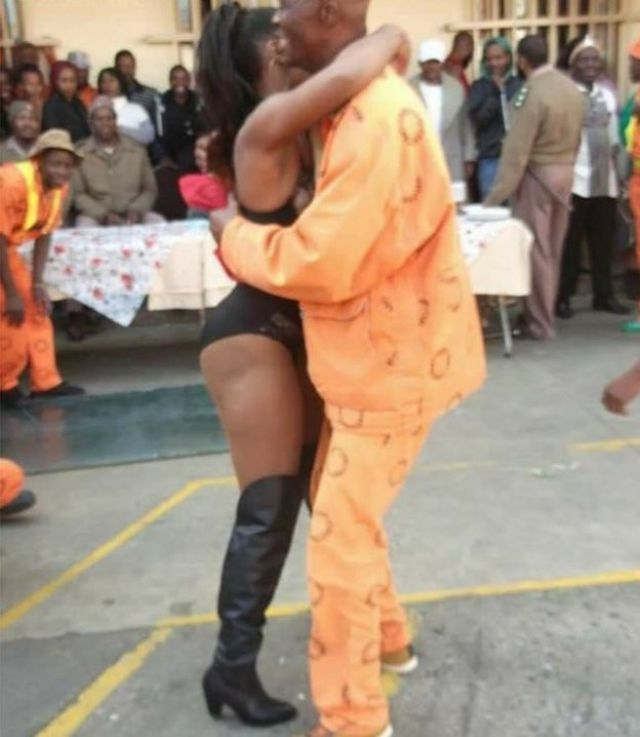 A woman cuddles up to an orange-suited prisoner