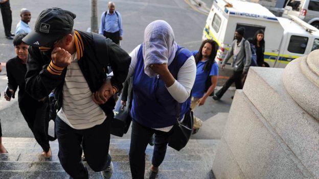 Lavona Solomon (le visage couvert) arrive à la Haute Cour du Cap pendant son procès.