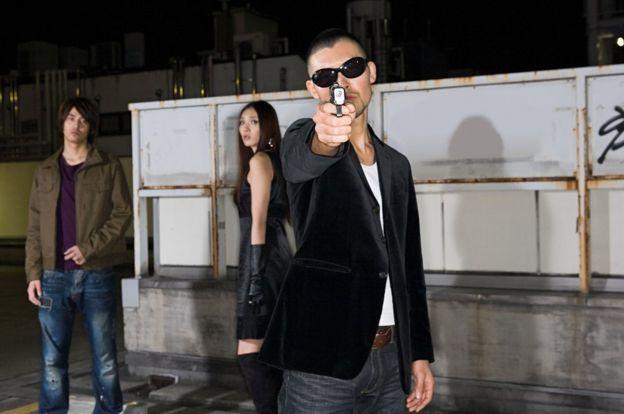 Japanese man points gun at camera