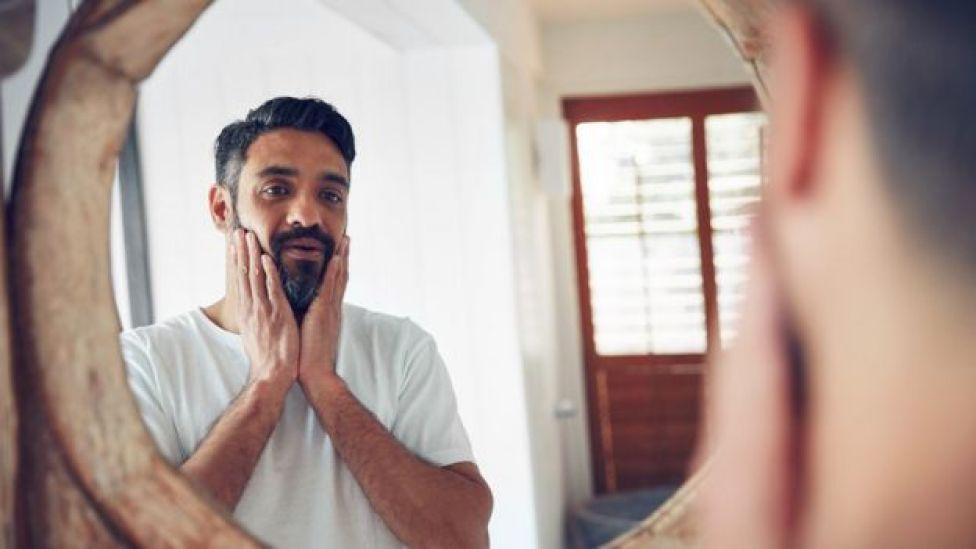 Hombre de mediana edad mirándose al espejo.