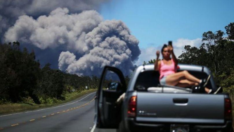 Imagem mostra mulher fazendo selfie com fumaça de vulcão ao fundo