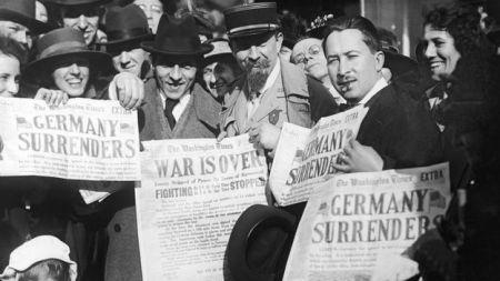 Schumpeter rodeado de pessoas que seguram uma página de jornal dizendo que a guerra acabou