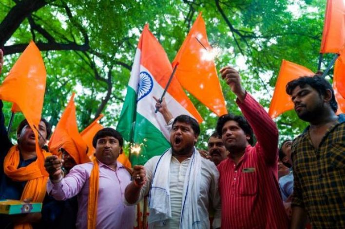Members of Hindu Sena, a rightwing group, celebrate after the abolition of Article 370 in Delhi