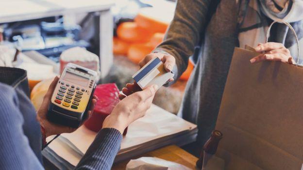 Em balcão, duas pessoas seguram um cartão de crédito e uma máquina de cartão