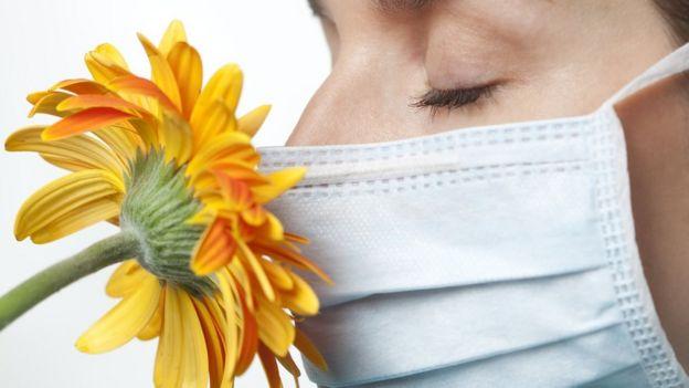 Mujer con mascarilla huele una flor