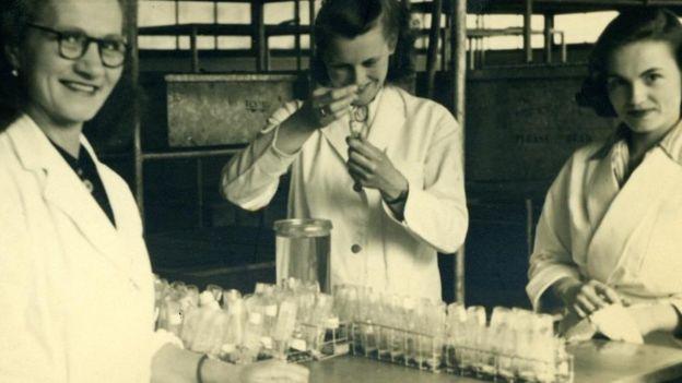 Tres científicas en batas blancas realizan pruebas inyectando sustancias en probetas