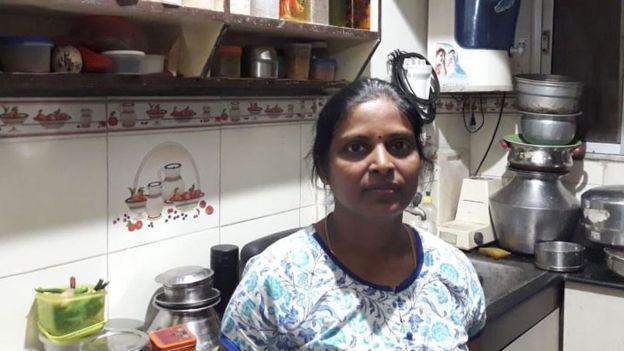 Shanthi debout dans sa cuisine