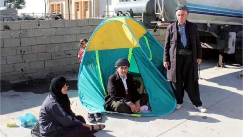 Man in doorway of tent pitched on street, with another man, a woman and a child visible around him