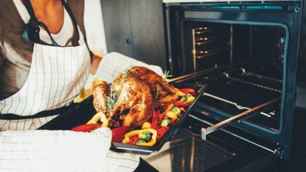 Mujer sacando un pollo del horno