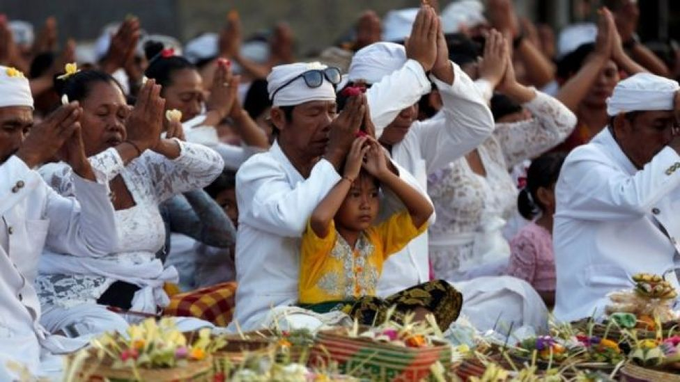Worshipers are pictured wearing white and praying cross legged.
