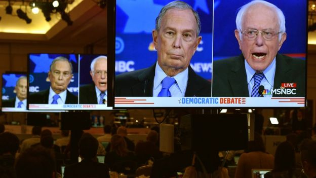TV screens showing Bloomberg and Sanders