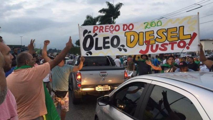 Manifestantes na porta de refinaria, ao lado de cartaz que pede: 'Preço do óleo diesel justo!'