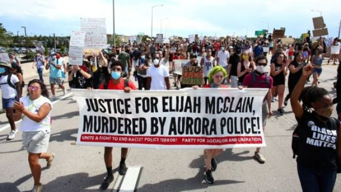 "Protesters march holding a banner that reads: ""Justice for Elijah McClain, murdered by Aurora Police!"""