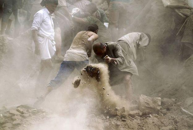 Civilians search through the rubble after a Saudi air strike