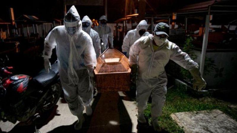 Homens protegidos com máscaras carregam caixão