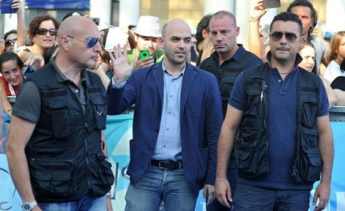 Roberto Saviano (centro) junto a tres guardaespaldas.