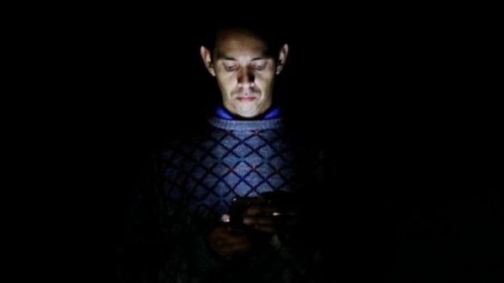 Homem iluminado pela luz de seu telefone