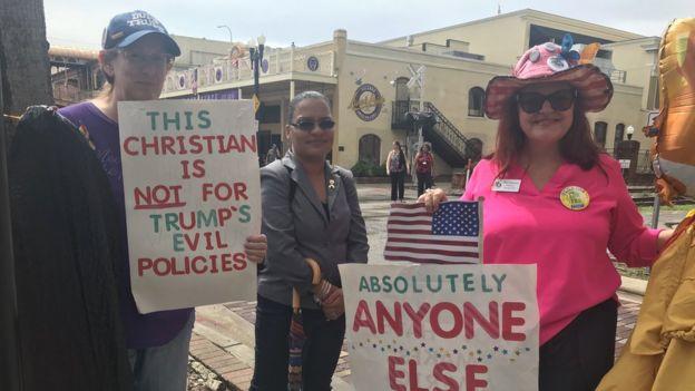 Tres muejres protestando conta Trump