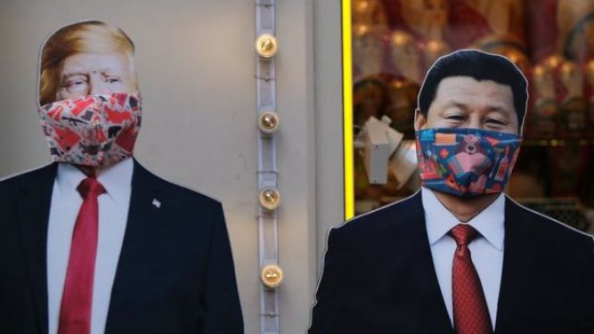 Cardboard cutouts of US President Donald Trump and Chinese President Xi Jinping, with protective masks widely used as a preventive measure against coronavirus disease (Covid-19), near a gift shop in Moscow, Russia