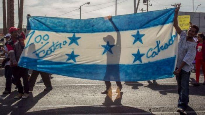 """Migrantes con bandera de Honduras y el lema """"100% catrachos""""."""