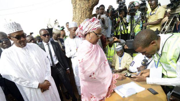 Aisha Buhari registers to vote as the president looks on