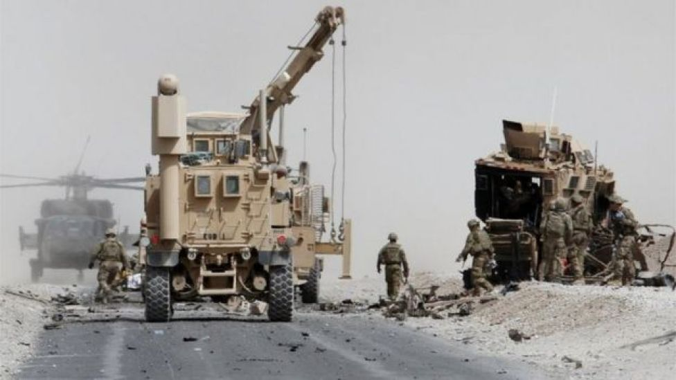 U.S. troops assess the damage to an armoured vehicle of NATO-led military coalition after a suicide attack in Kandahar province, Afghanistan August 2, 2017.