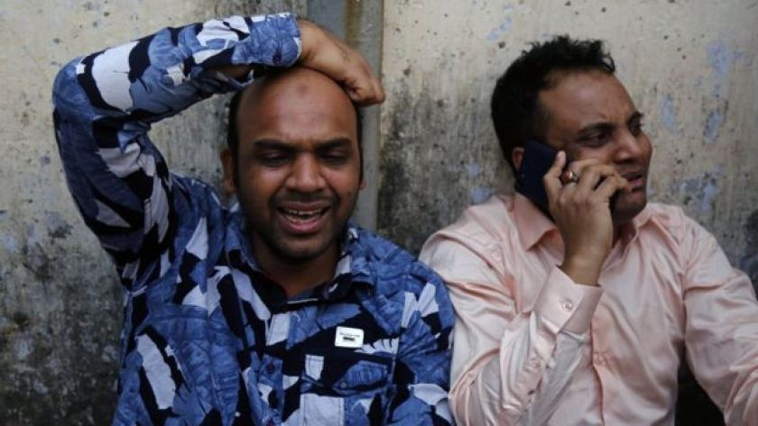 Two men grieve outside Dhaka Medical College