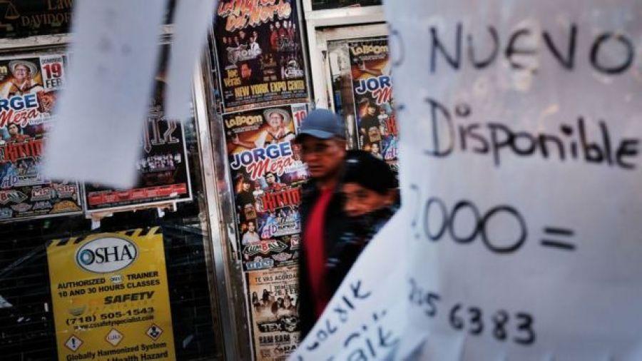 Dos personas caminan por un barrio latino de Queens, Nueva York.