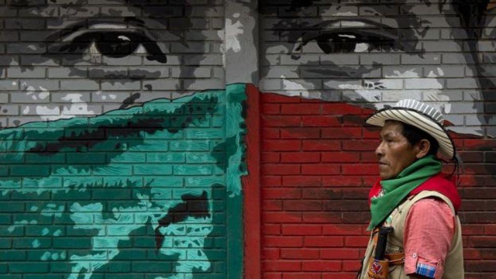 Un líder nasa pasa frente a un mural
