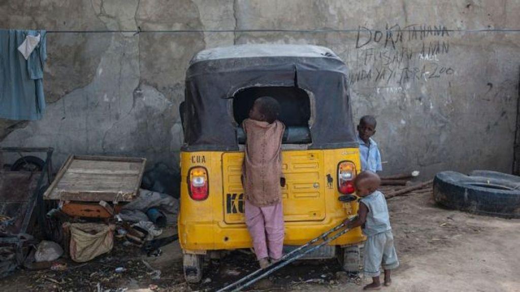 """أطفال يلعبون حول عربة """"توك توك"""" معطلة في مايدوغوري، شمال شرق نيجيريا"""