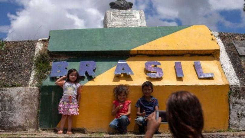 """Crianças venezuelanas posam para uma foto em frente a um monumento em Pacaraima que diz """"Brasil"""", com as cores do país"""