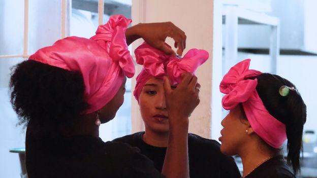 Mujeres que atienden en el restaurante, arreglándose los lazos fucsias que se ponen en la cabeza.
