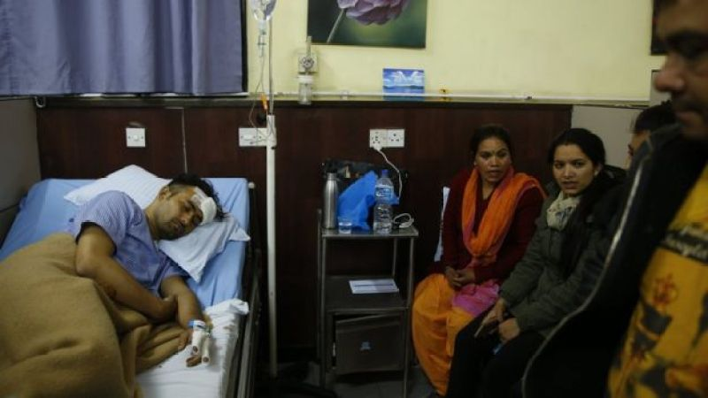 Basanta Bohora, who escaped the plane, sleeps in a hospital bed as family look on
