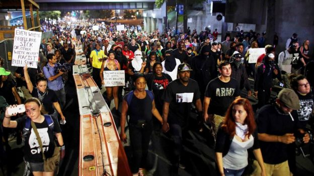 Protestors defied a curfew on Thursday night to protest against the shooting of Mr Scott