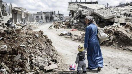 Mulher caminha com criança em meio a ruínas de cidade na Síria após conflito entre combatentes