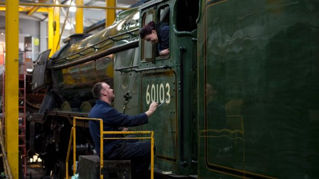 A workman paints the number 60103 on the cab of the Flying Scotsman while being watched by his daughter and colleague