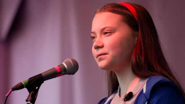 Greta Thunberg speaking in to a microphone at a rally.