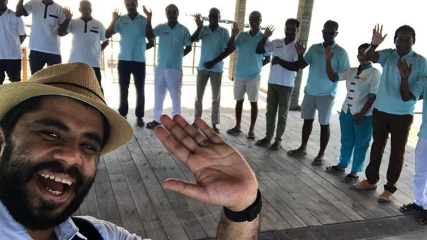 Khalid poses for a selfie with resort staff