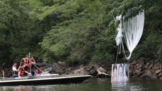 Police collect a balloon fallen in a river in South Korea