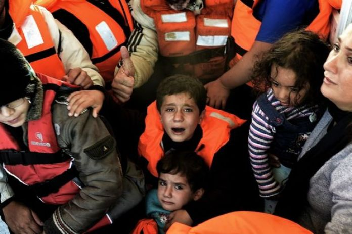 a crying boy in a lifejacket looks up at the camera