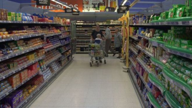 A woman shopping in a Sainsbury's grocery aisle