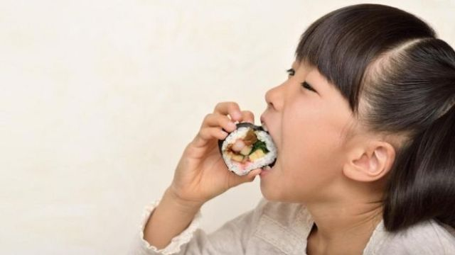 Menina come sushi