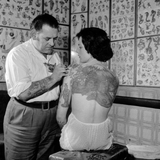 Tatuador tatuando hombro de Pam Nash