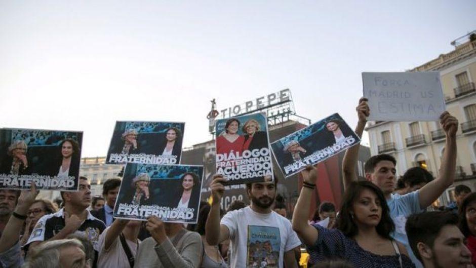 Los manifestantes en la Puerta del Sol de Madrid muestran el retrato de Carmena y Colau.