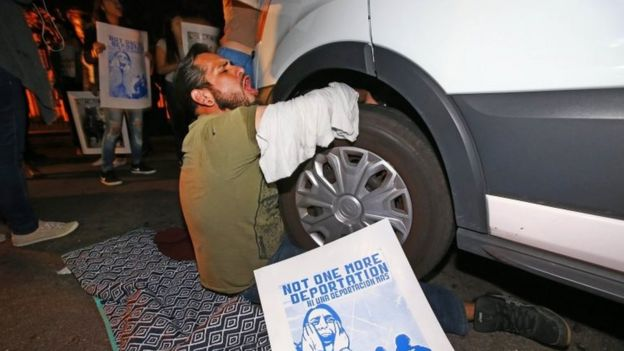 A protester locked himself to the van carrying Guadalupe Garcia de Rayos that is stopped by protesters outside the Immigration and Customs Enforcement facility, on 8 February in Phoenix