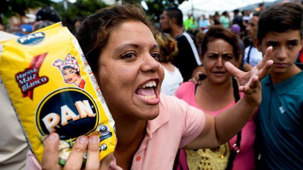 Una venezolana protesta con un kilo de harina de maíz precocida en la mano