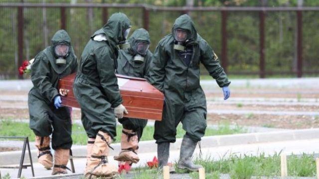 Pessoas carregam caixão usando roupas protetoras na Rússia