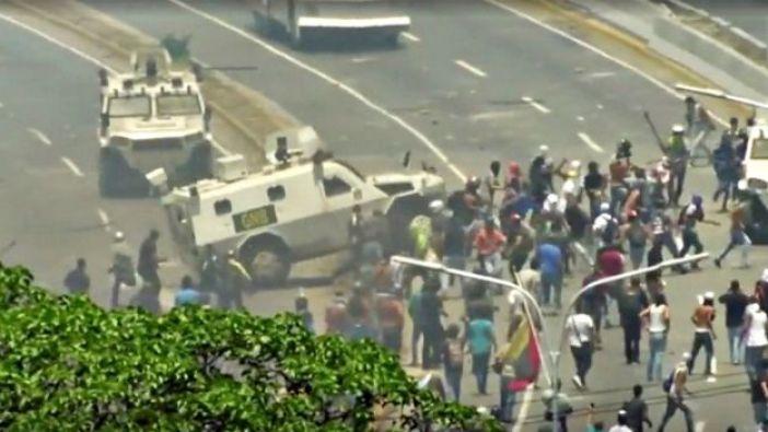 Una tanqueta arremetiendo en contra de manifestantes en Caracas.