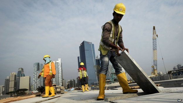 Migrant workers from India construct a road leading to the Financial District in Singapore, 4 February 2014