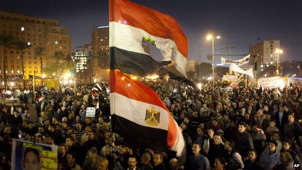 "Egyptians opposing president Mohammed Morsi fly their national flags as one holds a poster with a picture of a slain protester with Arabic that reads ""Martyr Mostafa Helmi, down with the rule of the Morshid,"" during a rally in Tahrir Square, Cairo, Egypt, Tuesday, Dec. 18, 2012"